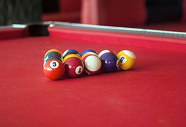 Billiards on a red topped table