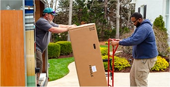 Men unloading a package from a truck.