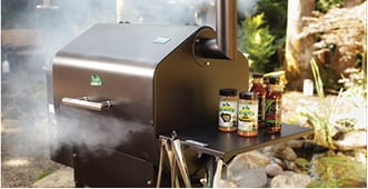 A smoking grill with spices on the side.