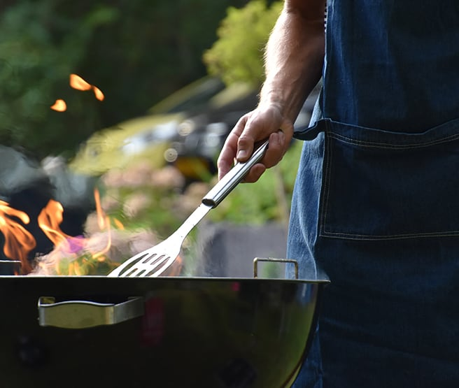 A man grilling over an open flame